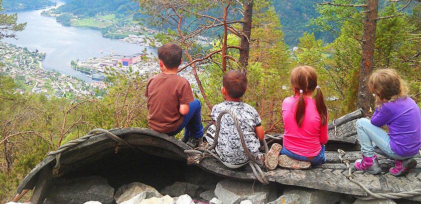 Barn som sitter på toppen av Hafstadkleiva og ser utover Førde nedenfor